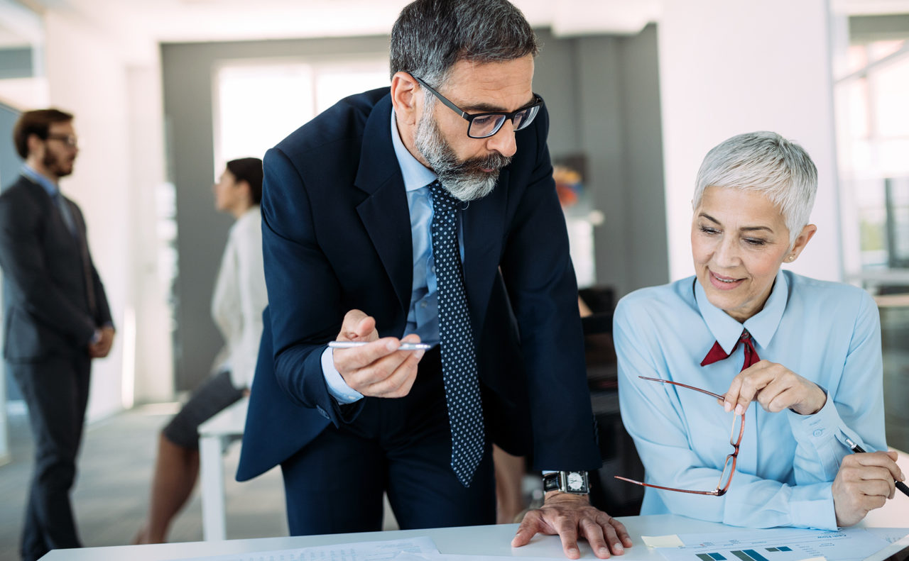 Happy mature businessman and businesswoman planning in modern office